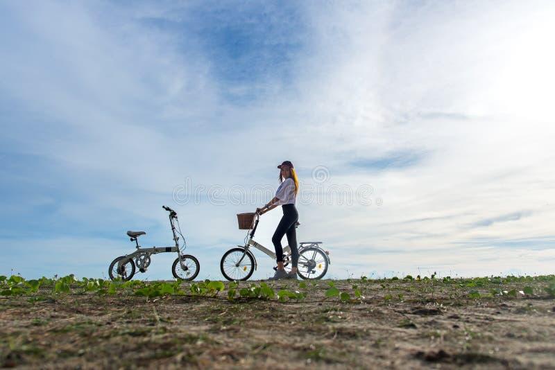 De glimlachende vrouw geniet van en ontspant met fiets die op strandzand berijden die pret en gelukkige, blauwe hemelachtergrond  royalty-vrije stock foto