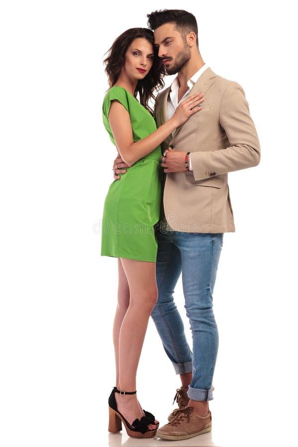 De glimlachende vrouw in groene kleding omhelst de haar elegante mens stock afbeeldingen