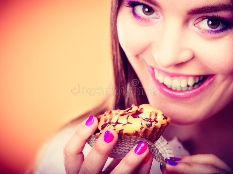De glimlachende vrouw houdt cake in hand stock afbeelding