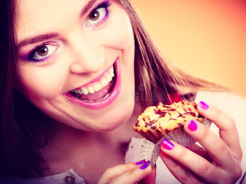 De glimlachende vrouw houdt cake in hand stock foto