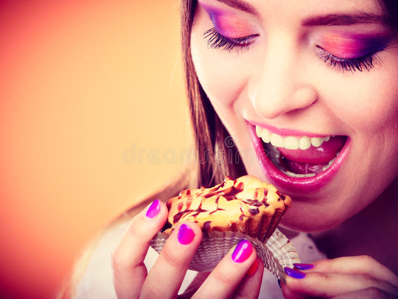 De glimlachende vrouw houdt cake in hand stock afbeeldingen