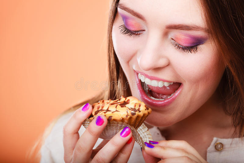 De glimlachende vrouw houdt cake in hand royalty-vrije stock afbeelding