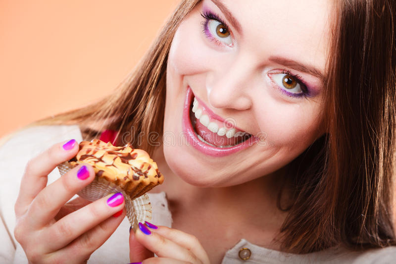 De glimlachende vrouw houdt cake in hand stock foto's