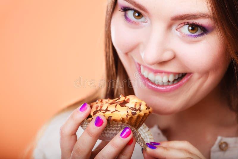 De glimlachende vrouw houdt cake in hand royalty-vrije stock foto