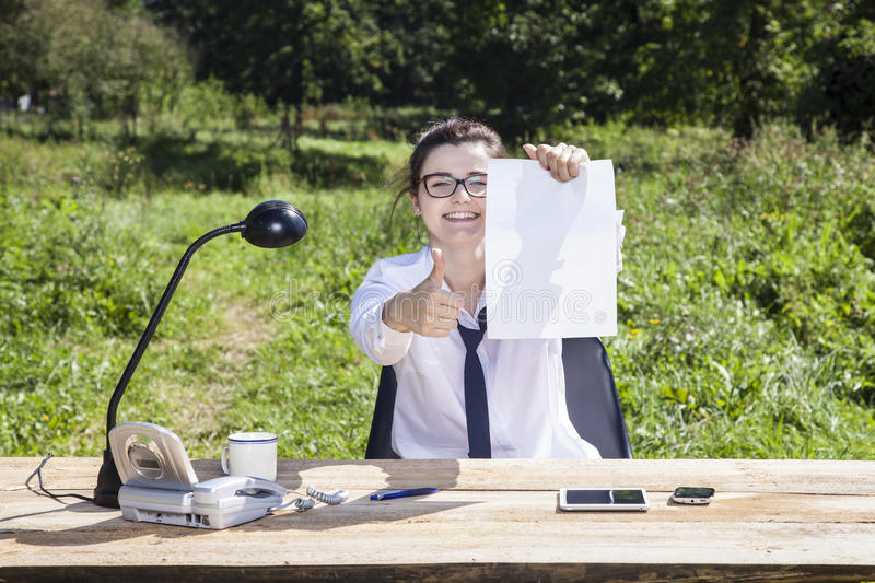 De glimlachende vrouw houdt een adreskaartje met ruimte voor reclame stock afbeeldingen
