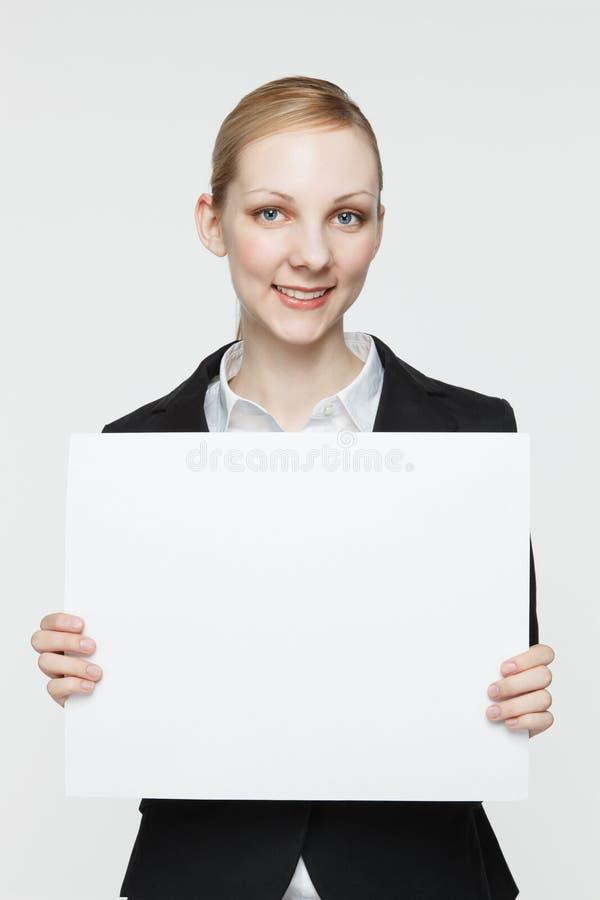 De glimlachende Vrouw houdt Leeg Teken stock fotografie