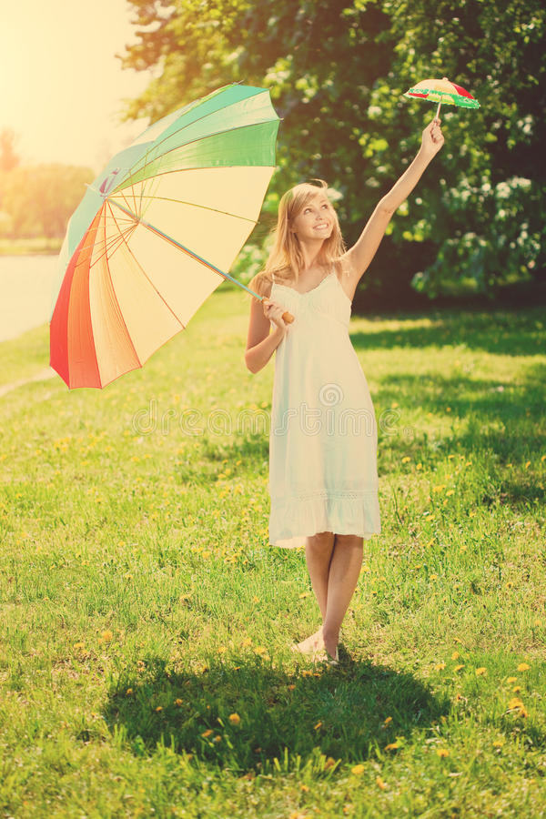 De glimlachende vrouw kiest in openlucht grote of kleine regenboogparaplu royalty-vrije stock foto