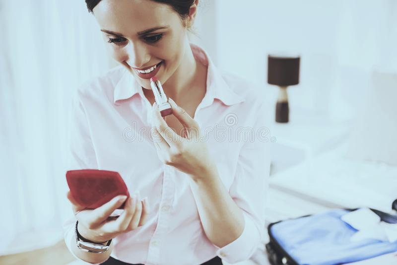 De glimlachende Vrouw kijkt in Spiegel en schildert haar Lippen stock foto