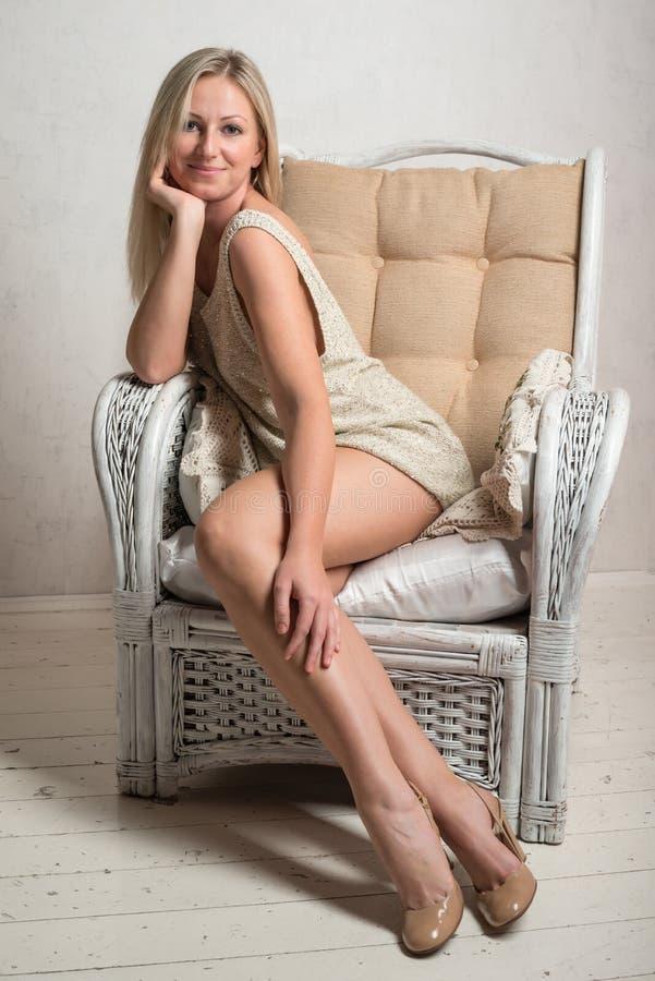 De glimlachende vrouw in korte kleding stelt op een stoel royalty-vrije stock afbeelding