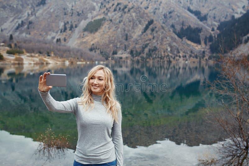 De glimlachende vrouw maakt selfie bij het meer stock foto's