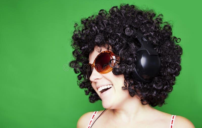 De glimlachende vrouw met afrohaar luistert aan muziek met hoofdtelefoons stock foto