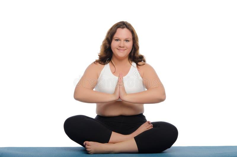 De glimlachende vrouw met overgewicht mediteert stock foto