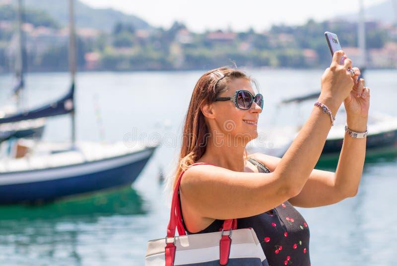 De glimlachende vrouw neemt een selfie dichtbij het meer stock foto's