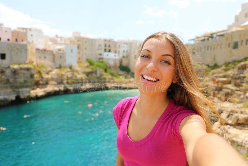 De glimlachende vrouw neemt zelfportret in haar de zomervakantie in Polignano een merrie, Middellandse Zee, Italië royalty-vrije stock afbeelding