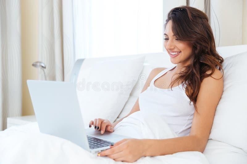 De glimlachende vrouw ontspant in bed met een laptop computer royalty-vrije stock afbeeldingen