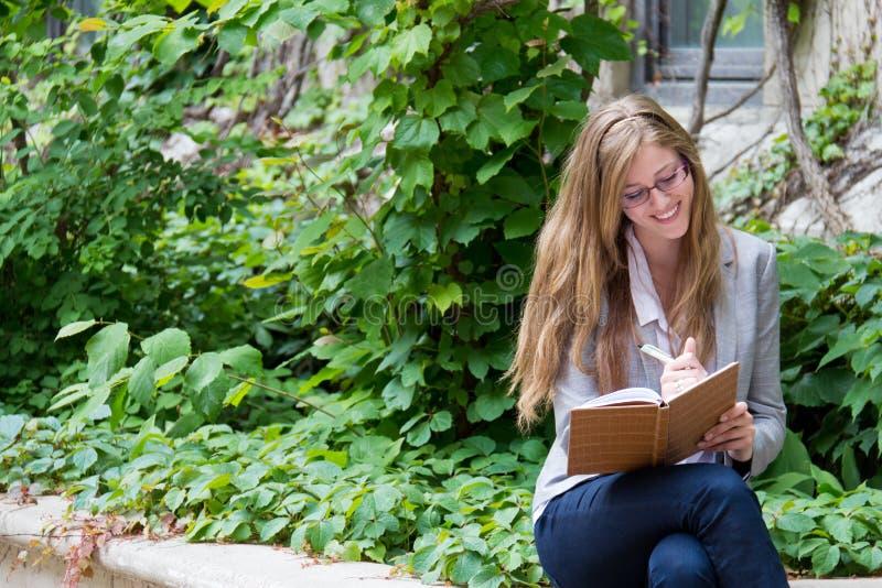 De glimlachende vrouw schrijft in haar dagboek royalty-vrije stock foto
