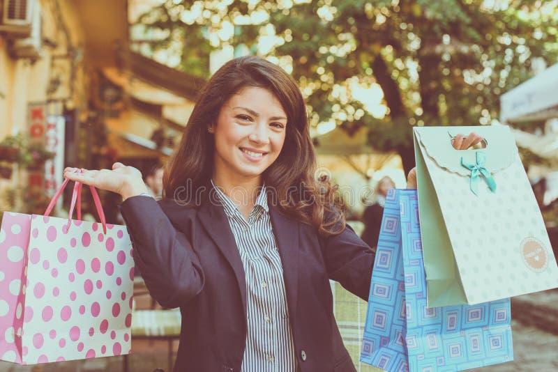 De glimlachende vrouw stelt aan camera met het winkelen zakken stock afbeeldingen