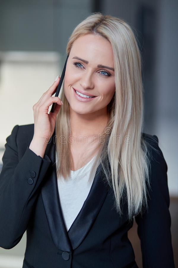 De glimlachende vrouw van de blonde middenleeftijd, leidende directeur die smartphonegesprek hebben royalty-vrije stock foto's