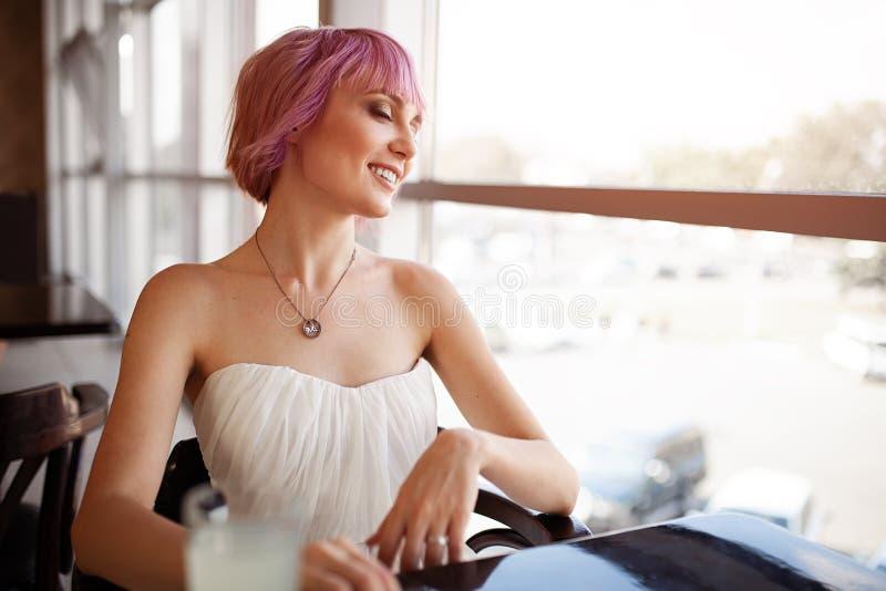 De glimlachende vrouw zit in comfortabele koffie-bar tijdens haar recreatietijd royalty-vrije stock afbeelding