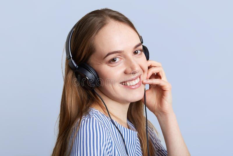 De glimlachende vrouwelijke exploitant met hoofdtelefoons gelukkig om cliënt te horen, verklaart iets met positieve uitdrukking,  royalty-vrije stock foto's