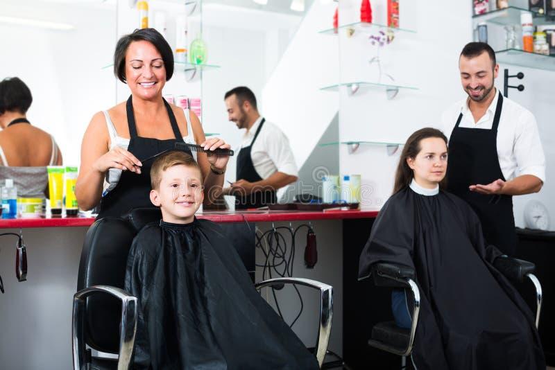 De glimlachende vrouwelijke leuke jongen van het kapper scherpe haar royalty-vrije stock foto