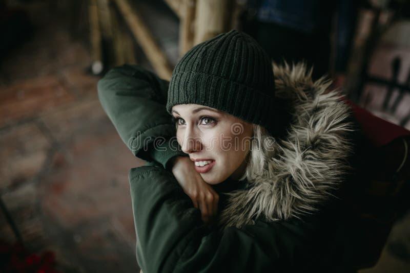 De glimlachende witte vrouw die green dragen breit hoed en laag, kijkend omhooggaande en het letten op stadslichten tijdens de na stock afbeeldingen