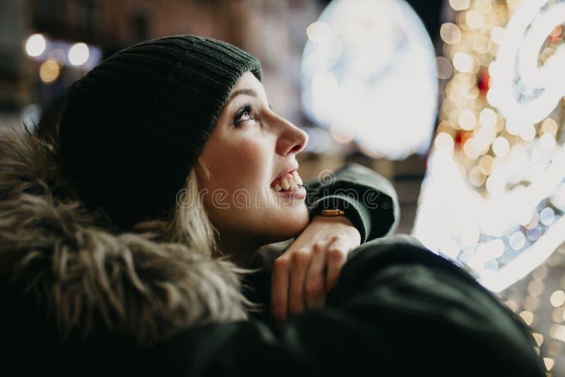 De glimlachende witte vrouw die green dragen breit hoed en laag, kijkend omhooggaande en het letten op stadslichten tijdens de na royalty-vrije stock foto