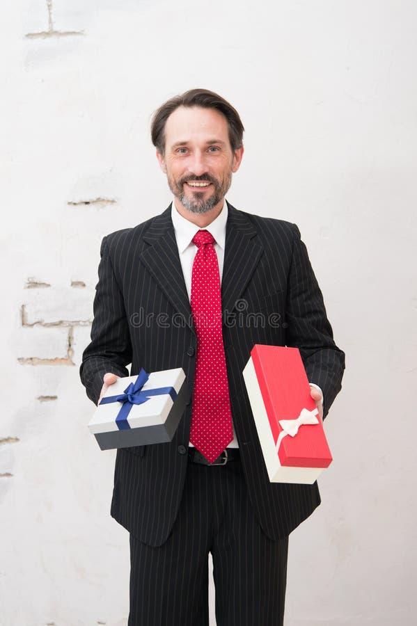 De glimlachende zakenman die twee houdt stelt en over juiste keus denkt voor stock afbeelding