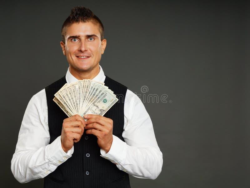 De glimlachende zakenman houdt geld stock foto's