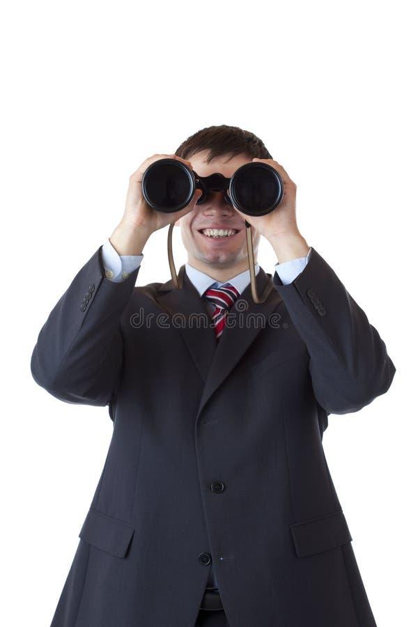 De glimlachende zakenman kijkt door verrekijkers stock fotografie