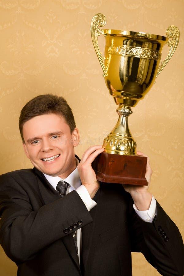 De glimlachende zakenman in kostuum met wint ter beschikking kop royalty-vrije stock afbeelding