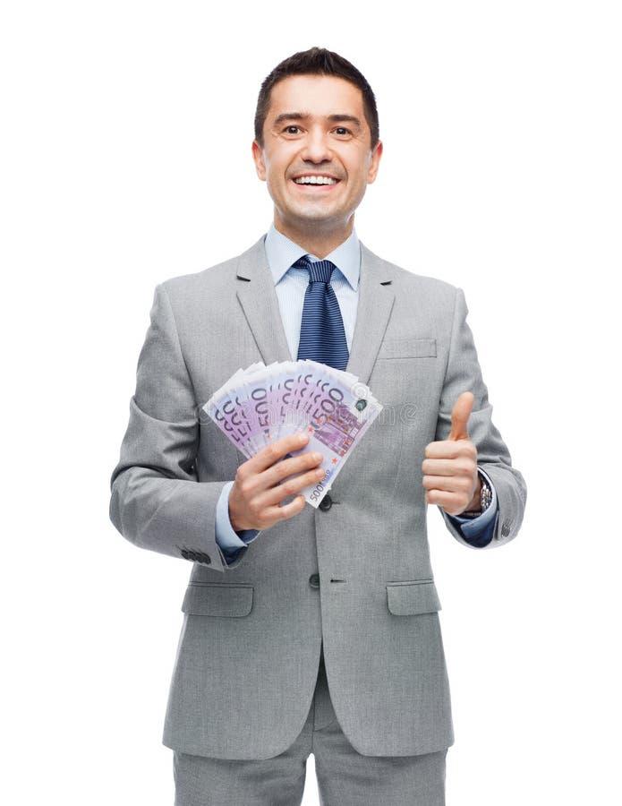 De glimlachende zakenman met geld het tonen beduimelt omhoog royalty-vrije stock afbeelding