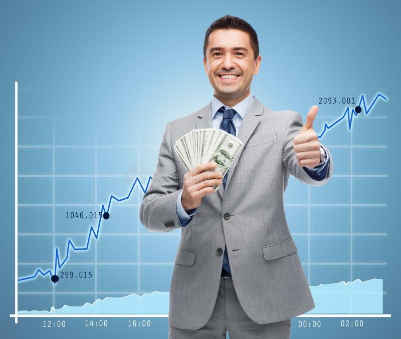De glimlachende zakenman met geld het tonen beduimelt omhoog stock afbeeldingen