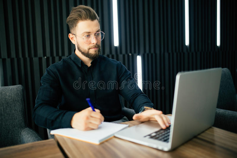 De glimlachende zakenman met laptop computer en schrijft bericht in documenten op kantoor royalty-vrije stock foto