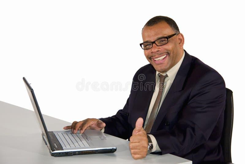 De glimlachende zakenman met laptop het stellen beduimelt omhoog stock foto's