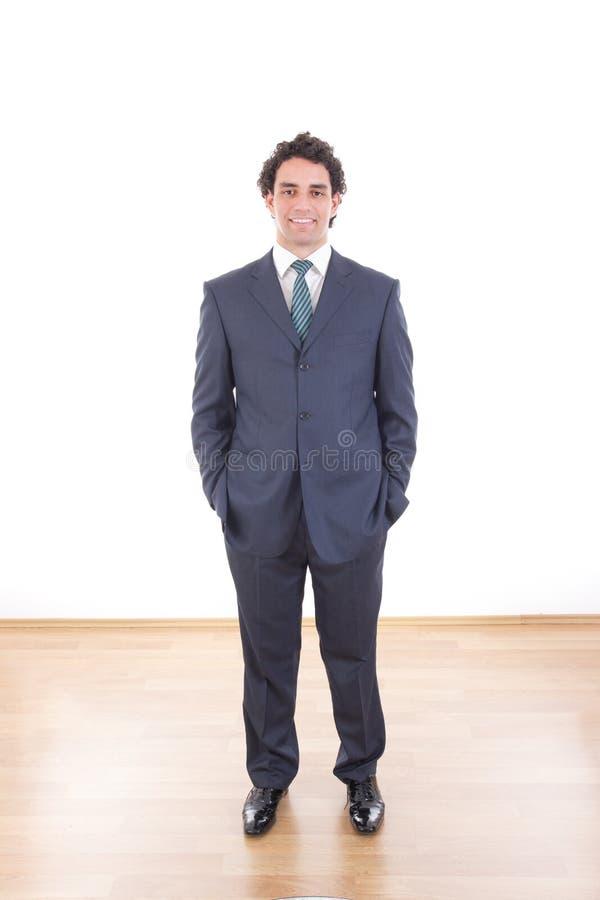 De glimlachende zakenman in zwart toevallig kostuum stelt bij studio stock afbeeldingen