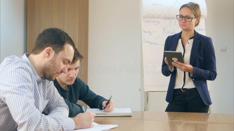 De glimlachende zekere vrouwelijke leraar met een tablet-PC hield in haar handen die zich voor klasse bevinden royalty-vrije stock fotografie