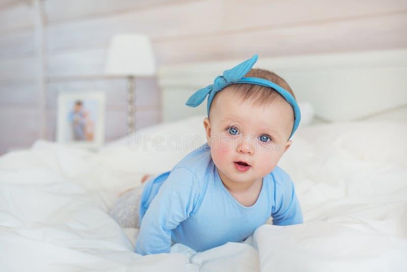 De glimlachende zuigeling in blauwe kleren kruipt op een bed in slaapkamer royalty-vrije stock afbeelding