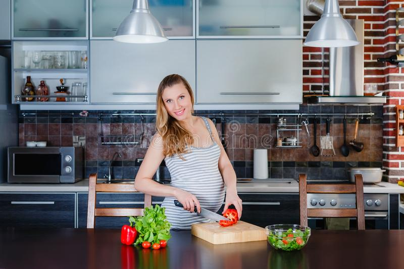 De Glimlachende zwangere vrouw in keuken kookt plantaardige salade royalty-vrije stock afbeelding