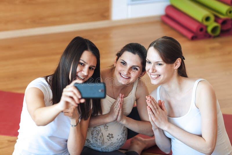 De glimlachende zwangere vrouwen nemen beelden van zich op een smartphone in de gymnastiek na een training royalty-vrije stock afbeelding