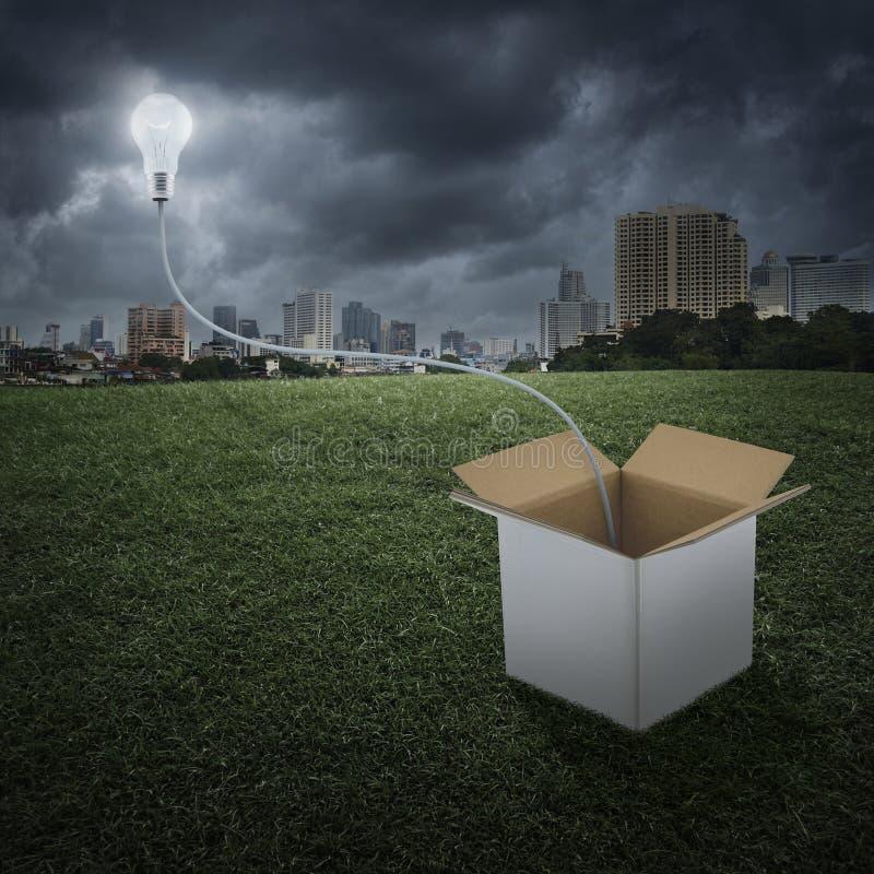 De gloeiende gloeilampenvlotter over doos op stad, denkt buiten de doos royalty-vrije illustratie