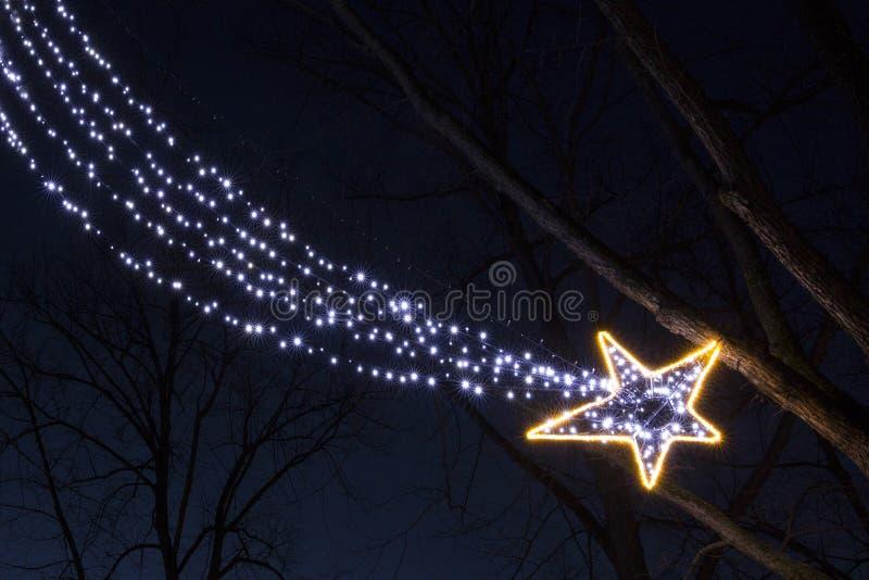 De gloeilampen dalende ster van de Kerstmisslinger in de nacht royalty-vrije stock afbeeldingen