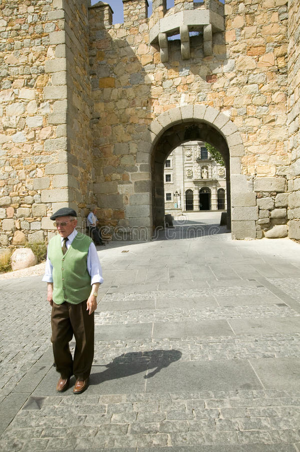 De goed-geklede oudere mens met hoed loopt door poort van ommuurde stad, Avila Spanje, een oud Kastiliaans Spaans dorp stock foto