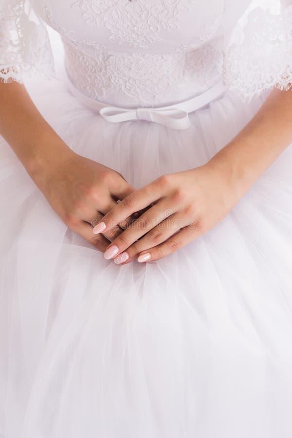 De goed-verzorgde handen van de bruid met een mooie manicure zijn op een witte huwelijkskleding royalty-vrije stock foto