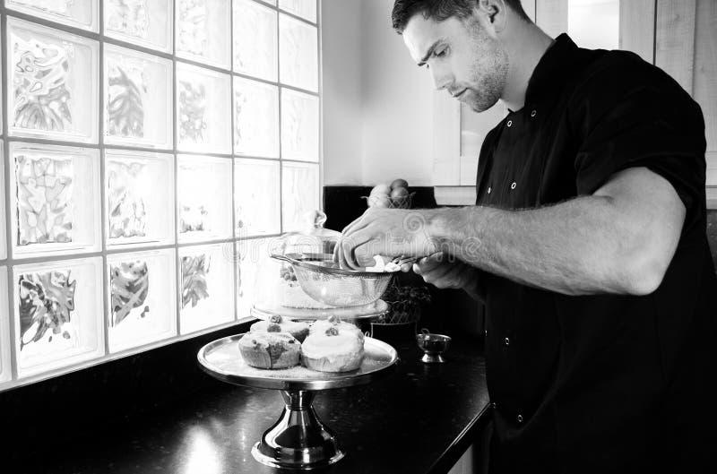 De goede loooking suiker van het bakkers bezige bestrooiende suikerglazuur op bevroren broodjes stock foto's