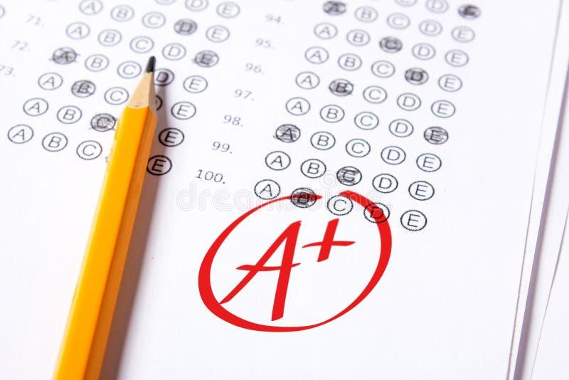 De goede rang van A plus wordt geschreven met rode pen op de tests royalty-vrije stock foto
