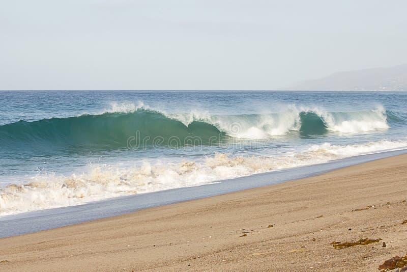 De golf van de Breeakingsbuis met schuim het creasting naar oever met terugslag op zandig strand royalty-vrije stock afbeelding