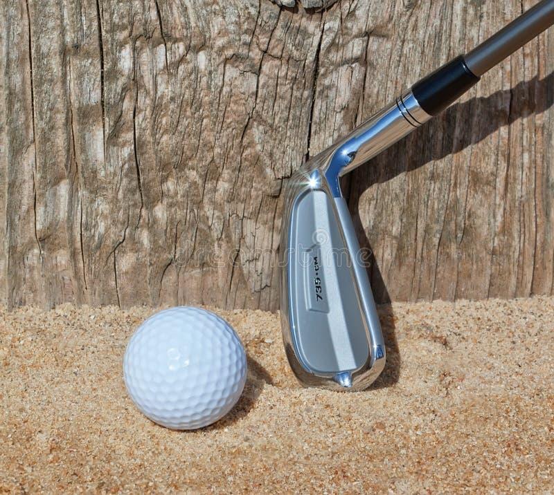 De golfbal en de stok keerden houten steun in het zand om. stock afbeelding
