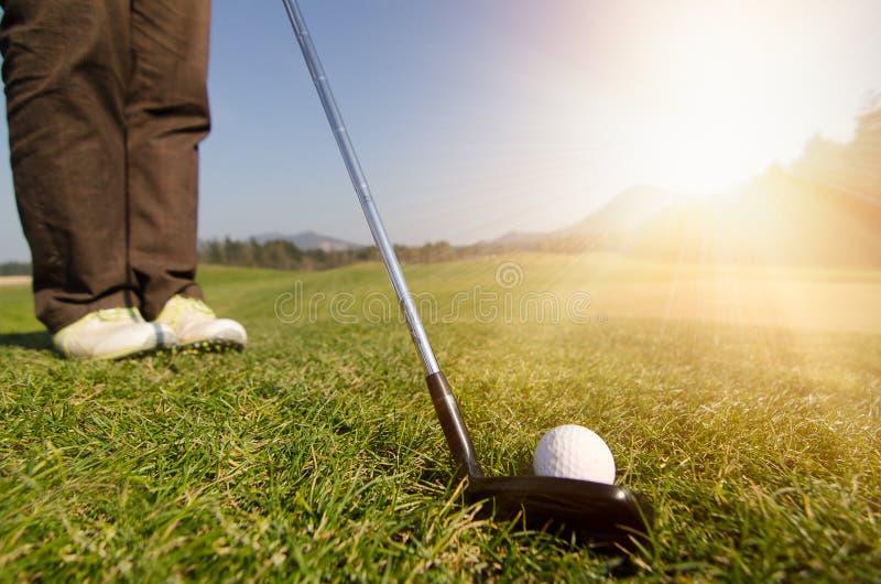 De golfspeler breekt een golfbal op green met bestuurdersgolfclub af royalty-vrije stock afbeelding