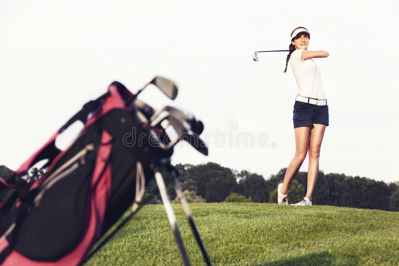De golfspeler die van het meisje de bal op golfcursus raakt. royalty-vrije stock foto's